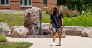 A college student is walking across campus while wearing a face mask