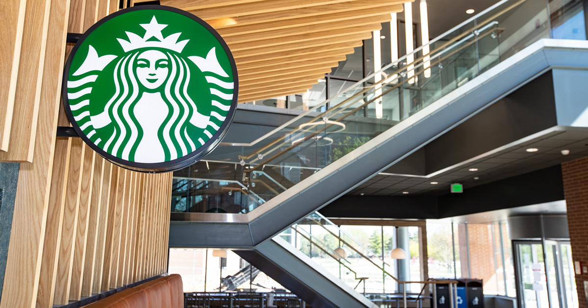 A Starbucks sign inside a large atrium with a staircase and large windows