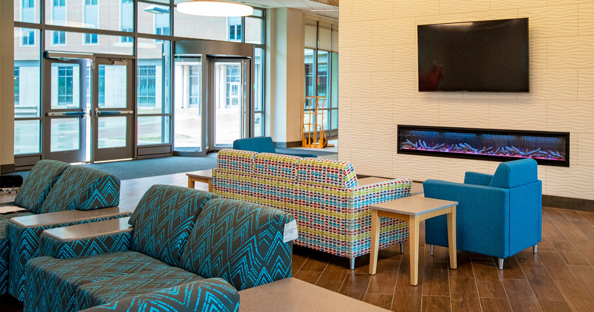 Building interior featuring bright blue furniture, large glass doors and walls, and a fireplace