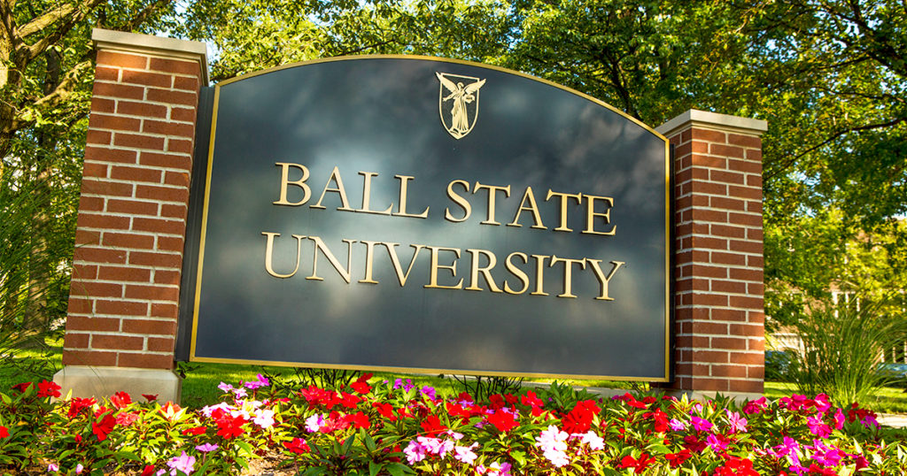 """A """"Ball State University"""" sign is surrounded by flowers and trees"""