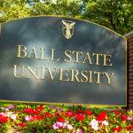 "A ""Ball State University"" sign is surrounded by flowers and trees"