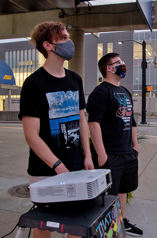 Two students next to a projector outdoors