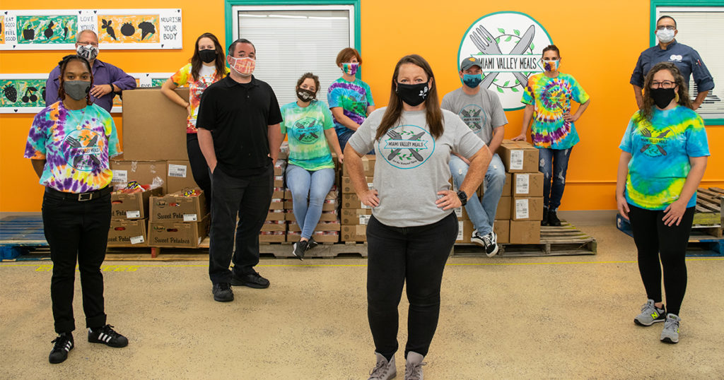 11 people stand in a brightly-colored kitchen while wearing masks