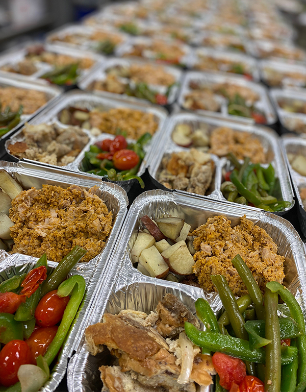 Trays full of food, including vegetables, grains, and meat