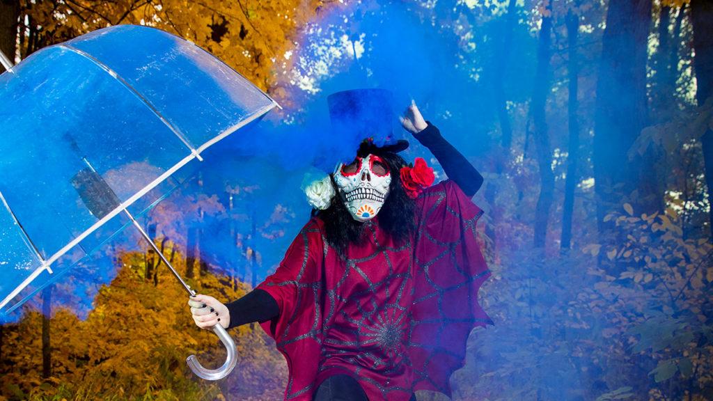 Woman wearing skeleton mask holding an umbrella in blue smoke.