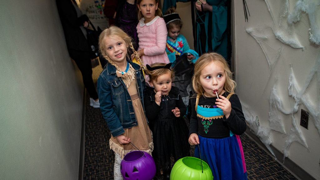 Children trick or treating while eating suckers.
