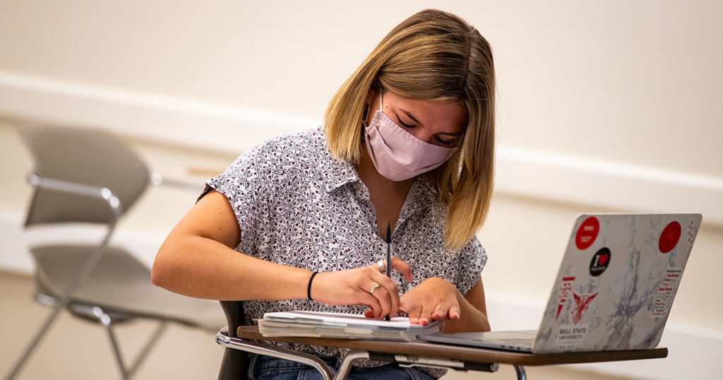 Student wearing a mask and sitting at desk with laptop.