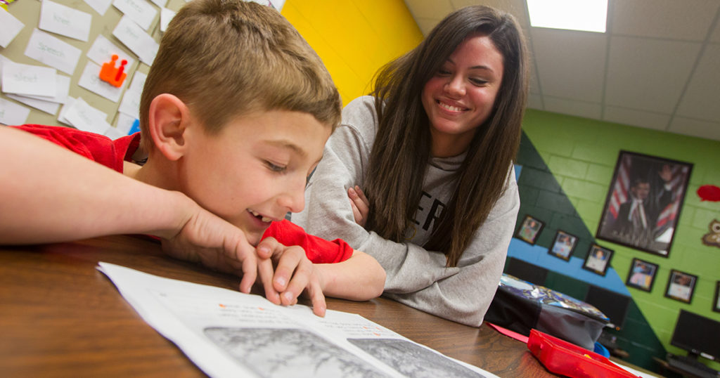 A child and teacher in a classroom setting