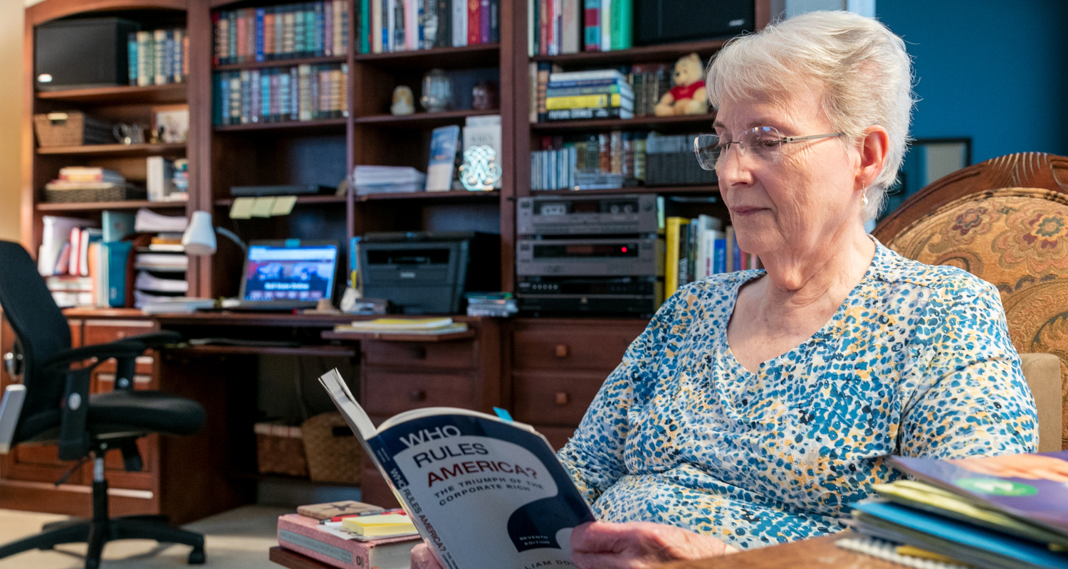 """Jane reading """"Who Rules America?"""" in a home office"""