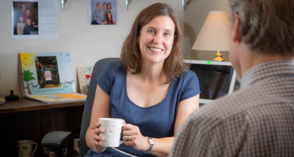 Dr. Bradley-Levine talking with a man in an office while holding a mug