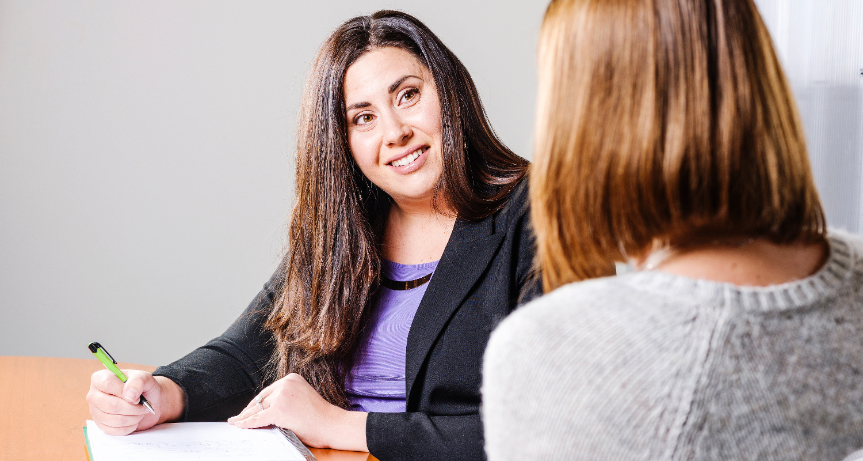 Deborah smiling at another woman while writing