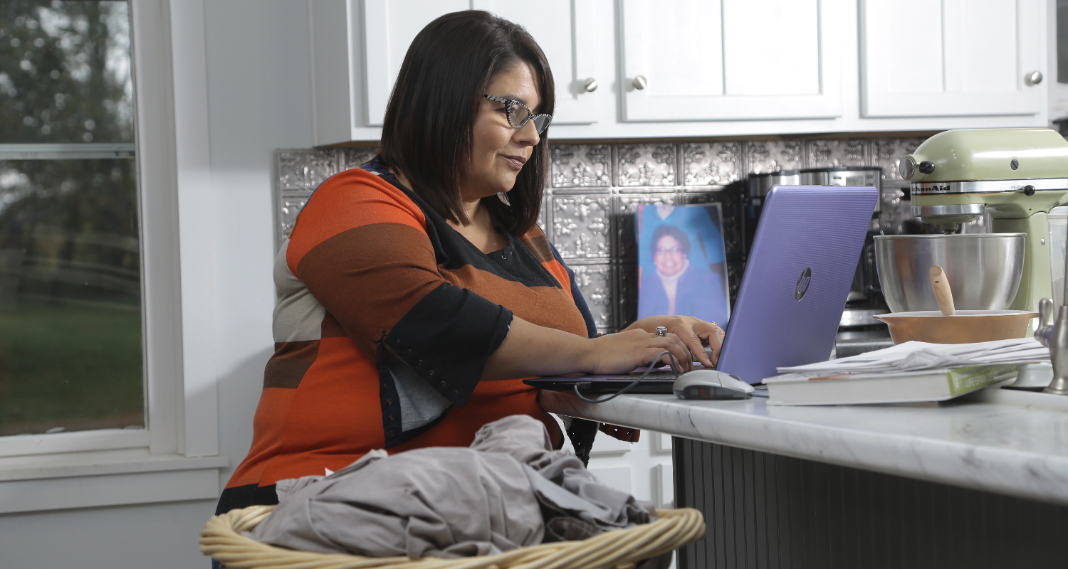 Kat typing on a laptop in a kitchen at home
