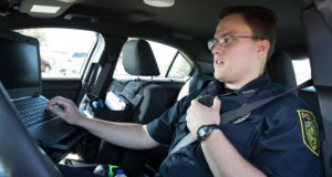 Jason in uniform while in the driver's seat of a police vehicle