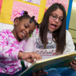 Brianna reading to a young child