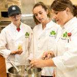 Three women in chef coats looking at a pot