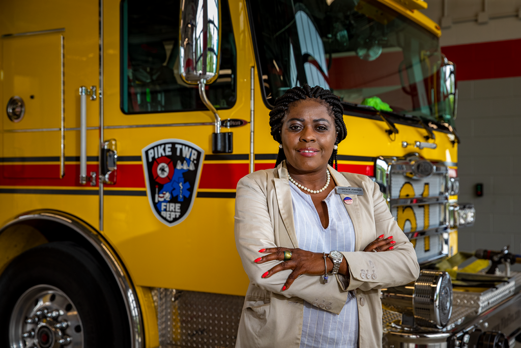Woman with arms cross standing in front of firetruck