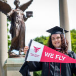 "Kaitlynn Holmes holding a ""We Fly"" pennant in front of the Beneficence statue"