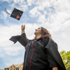 Kaitlynn Holmes in academic regalia tossing her graduation cap into the air