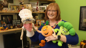 Carol Friesen holding puppets that she uses to educate young children about nutrition