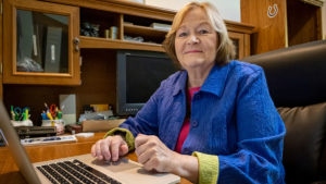 Ann Leitze seated in an office with laptop