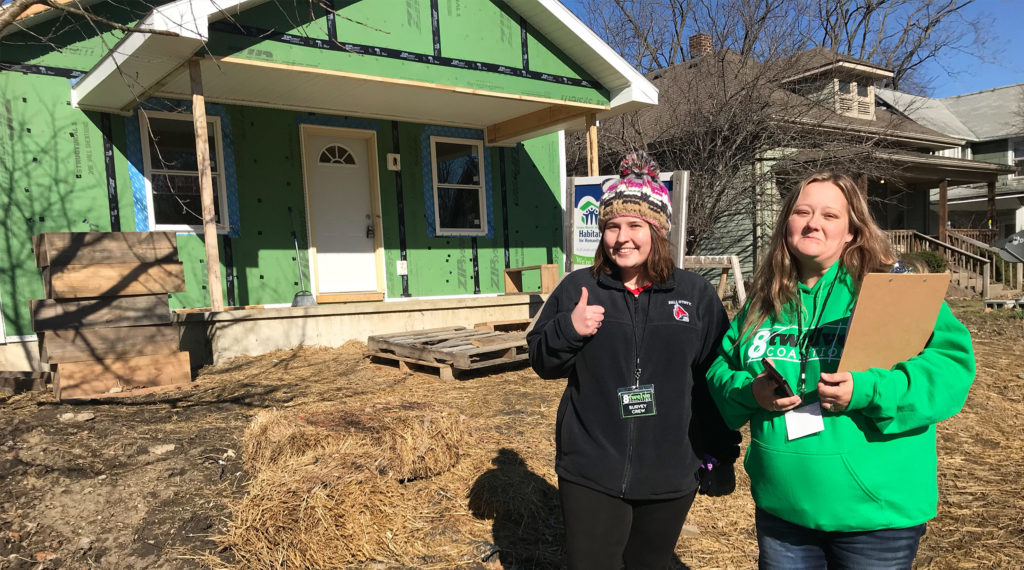 Volunteers pose in front of a house they are renovating