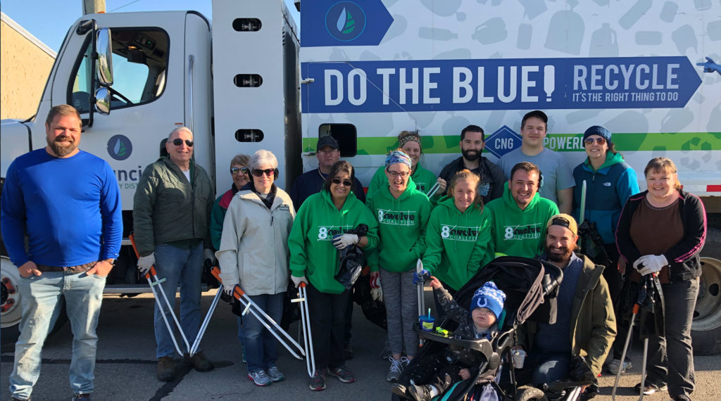 Group of volunteers pose in front of recycling truck