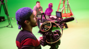 Camera Operator filming on a green screen set