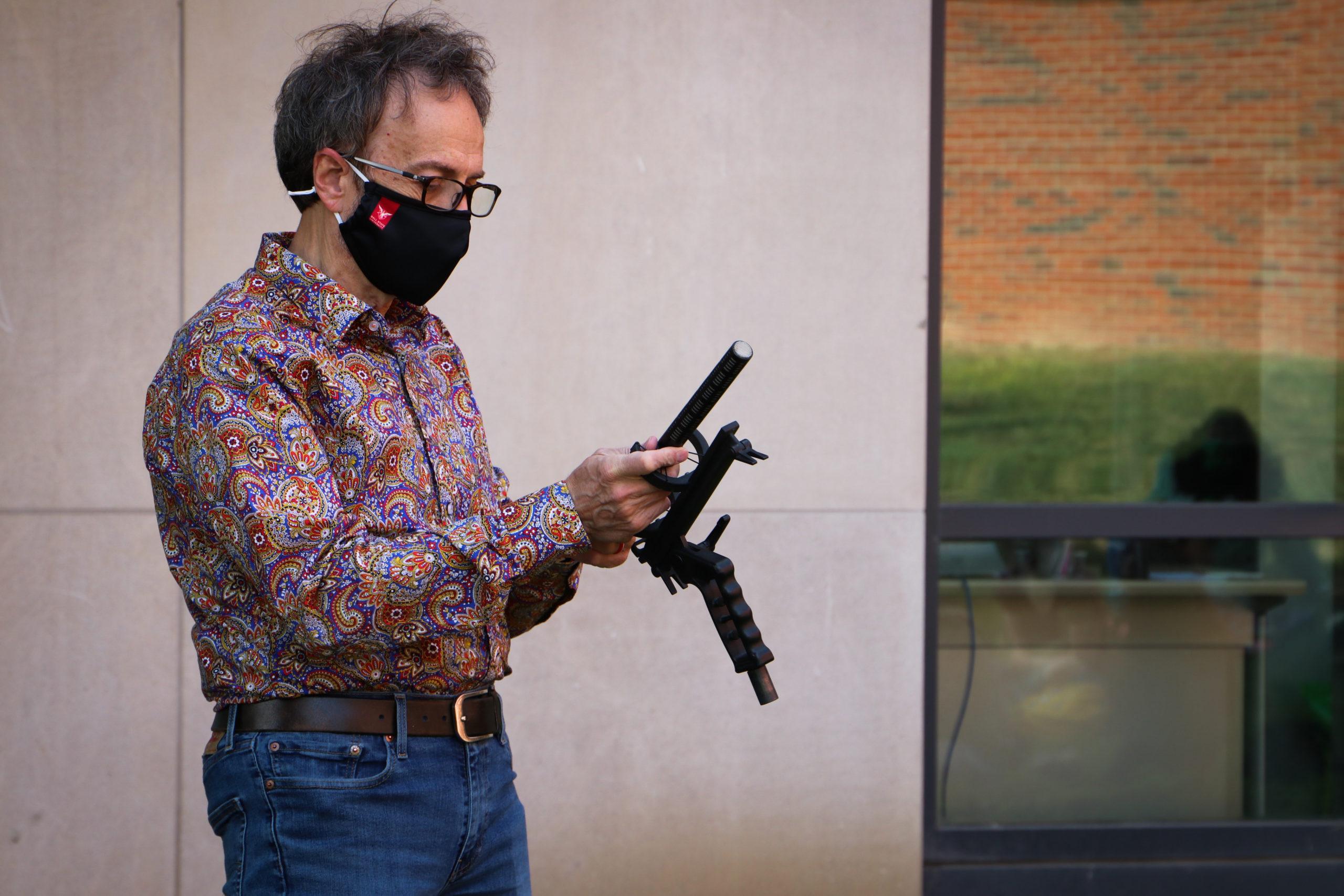 Stan Sollars holding a shotgun microphone.