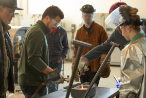 Students pouring glass into molds at the Marilyn K. Glick Center for Glass