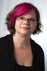 a woman with glasses and magenta hair
