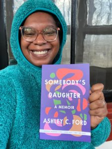 black woman in a teal hoodie holding a book